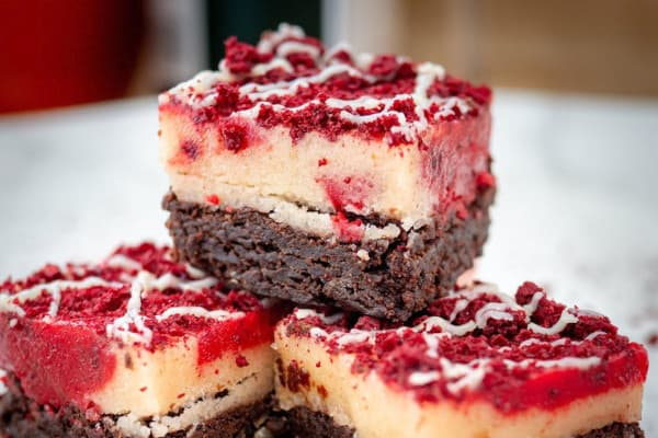 Three brownies stack on top of each other with a red topping