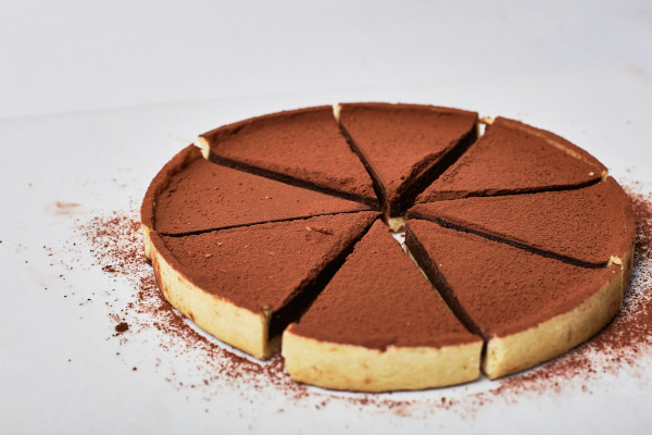 Dark chocolate tart cut up into slices against a white background