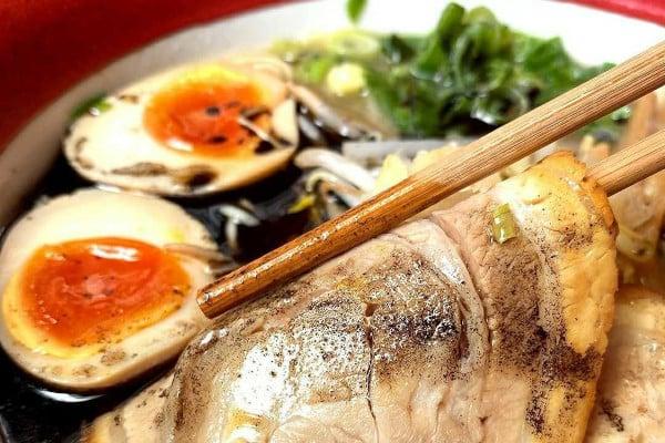 Chopsticks picking up a piece of pork in a ramen dish