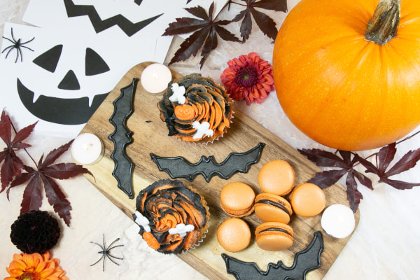 Halloween-themed treats on a wooden board with a pumpkin