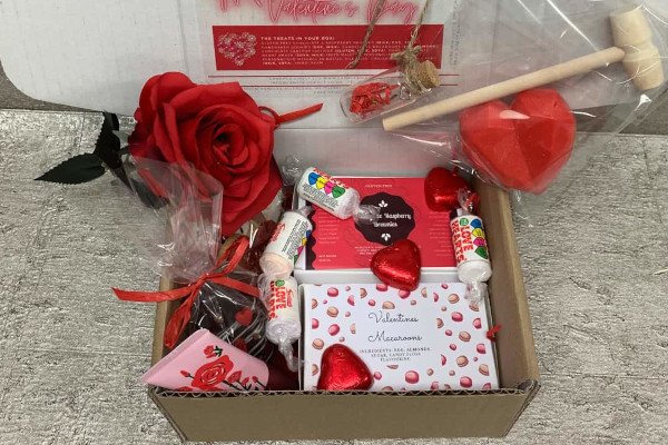 box filled with Valentine's treats like chocolate hearts, roses, hand cream, and macaroons