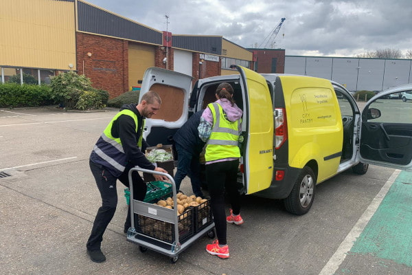Two City Harvest volunteers packing boxes of potatoes into a yellow City Pantry van