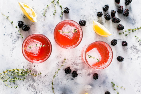Birds eye view of three red cocktails with blackberries scattered around