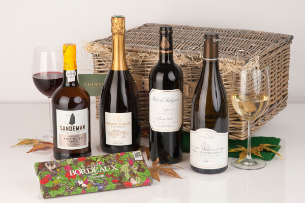 Wine bottles in front of a wicker hamper