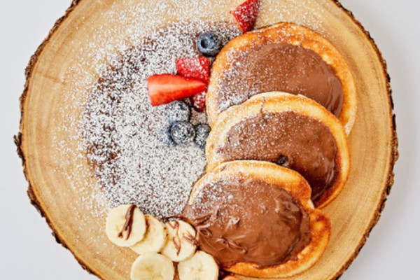 three american style pancakes on wooden board, topped with Nutella and fruit