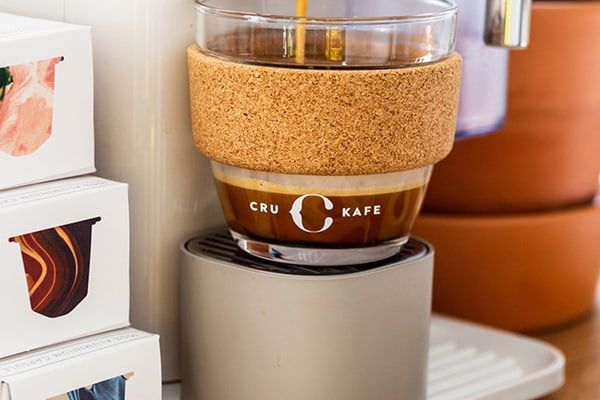 Coffee machine making coffee into a glass reusable coffee cup