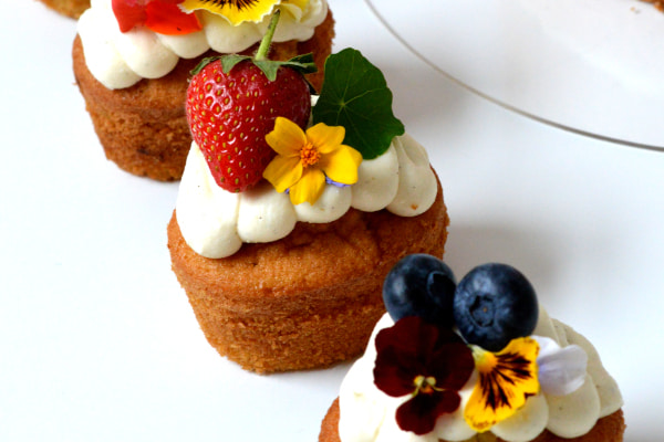 Three cupcakes decorated with frosting, fruits, and flowers