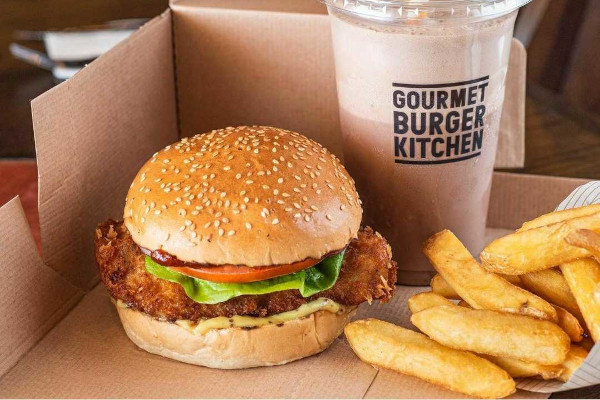 Chicken burger, fries and a milkshake in a cardboard takeaway container