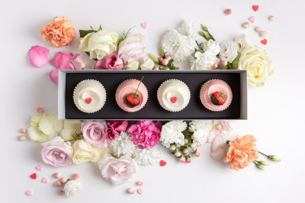 Box of cupcakes decorated with strawberries and heart sprinkles, surrounded by flowers
