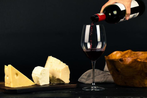 Red wine being poured into glass next to cheese board