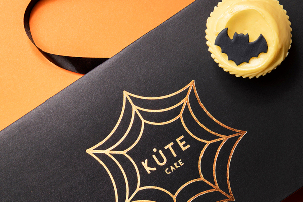Black box with Kute Cake logo inside spider web and yellow cupcake with bat on top