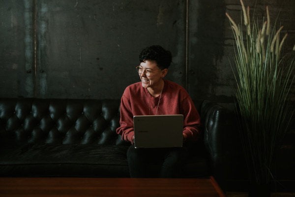 Person laughing while sat on sofa with laptop on their lap