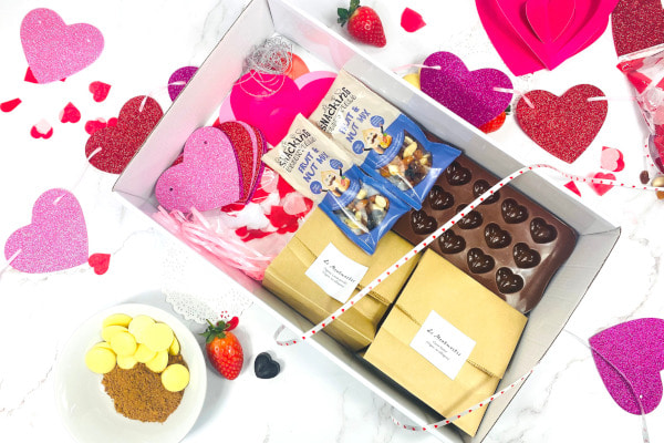 Box filled with ingredients and tools for creating valentines chocolates