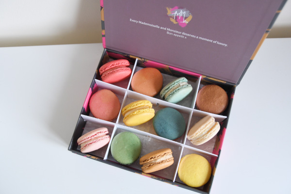 pastel-coloured macarons in a box
