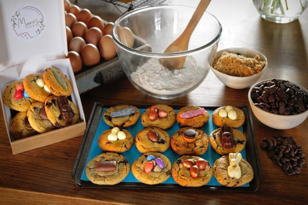 Decorated cookies on a baking tray surrounded by ingredients
