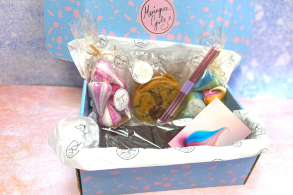 Pastel coloured box filled with cookies, brownies, meringues, and candles