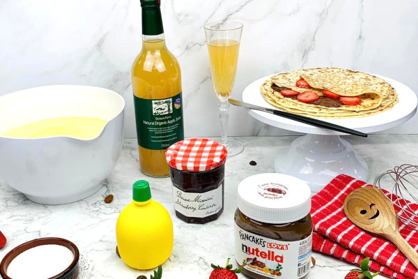 Pancakes on a plate surrounded by toppings and a bottle of juice
