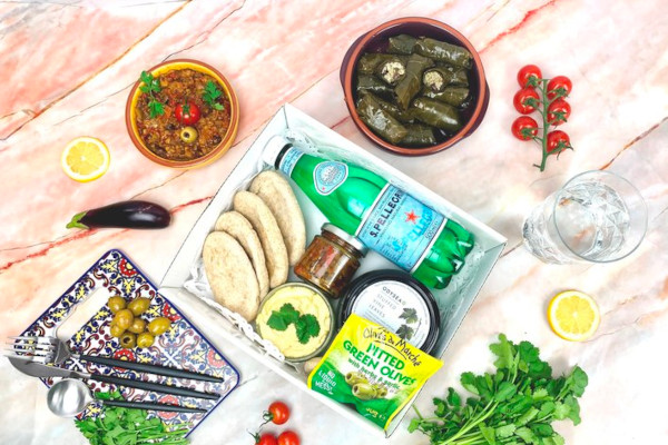 Box filled with bottled drink, pittas, olives, and spreads