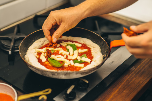 Hands adding ingredients to pizza in a frying pan