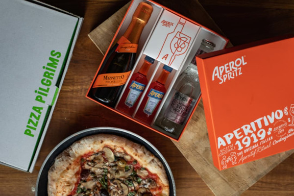Pizza in a frying pan and spritz kit in an orange box