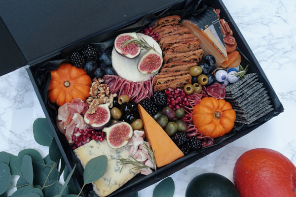 Box filled with cheese, crackers, cold meats, and pumpkins