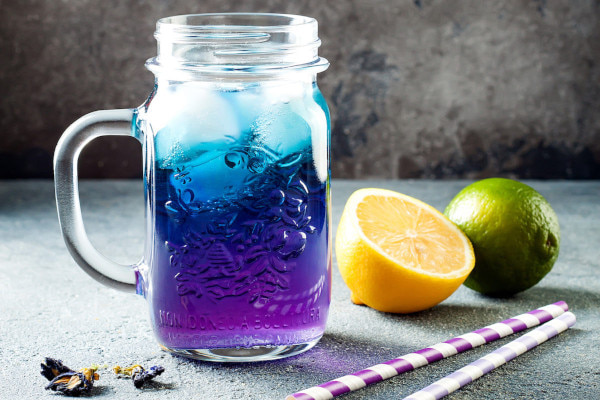 Colourful lemonade in a glass jar with paper straws