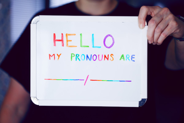 Person holding up sign saying 'hello my pronouns are'
