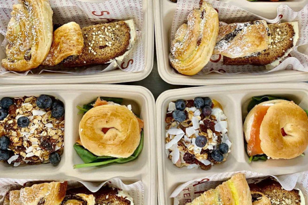 Boxes filed with bagels, banana bread, and pastries