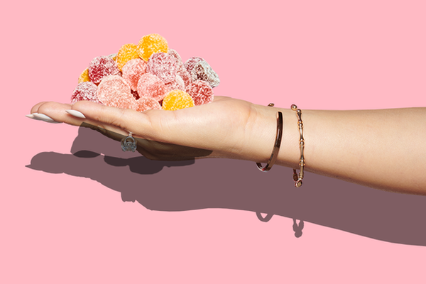 Hand holding pile of gummy sweets in front of a baby pink background