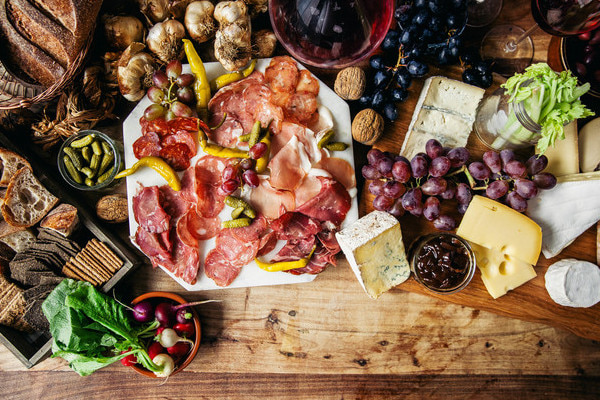 Wooden table with plates of cheese, crackers, and cold meats on top