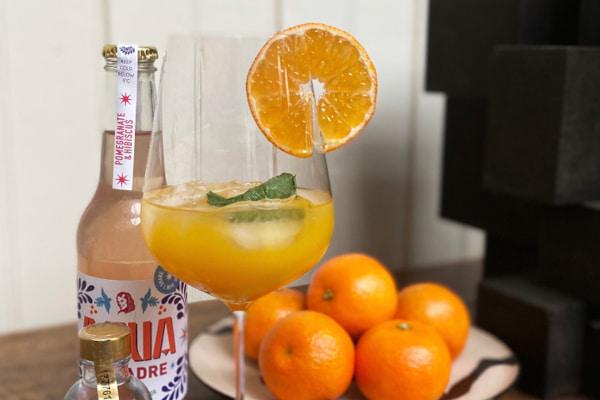 agua de madre bottle next to orange mocktail and oranges