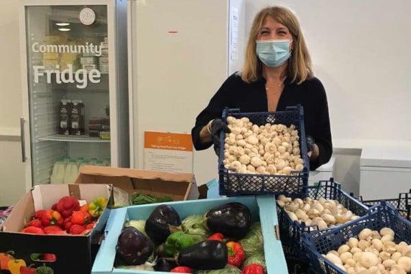 Volunteer at Albrighton Community Fridge holding up donated food