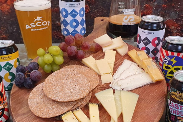 Cheese board with cans of craft beer