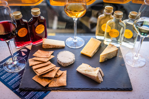 Cheeses on a slate board with bottles of wine