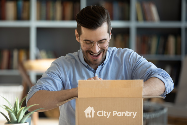 Person opening box with City Pantry logo, smiling and looking inside