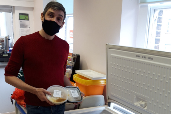 Clockhouse volunteer wearing mask and holding food boxes