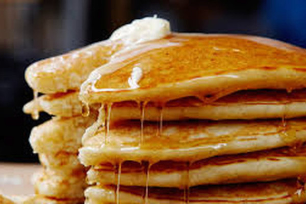 Pancakes stacked up with butter and syrup
