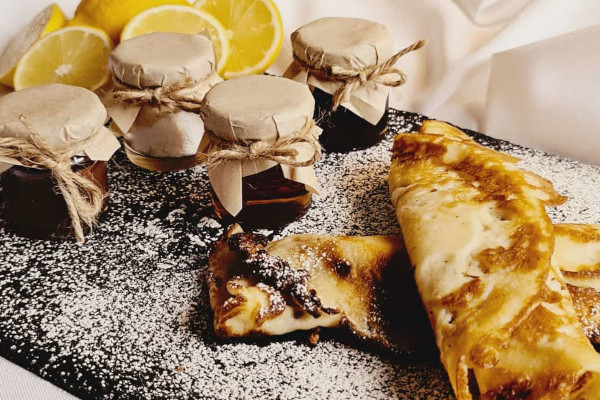Rolled up pancakes on slate board with dusting of icing sugar next to pots of jam and lemon slices