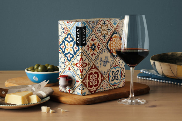 Glass of red wine next to an ornately decorated box