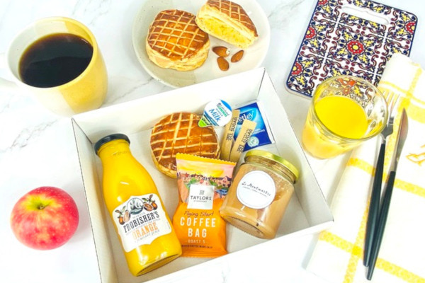 Breakfast box filled with juice, pastry, coffee, and more