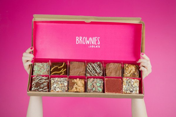 Hands holding up pink box of brownies