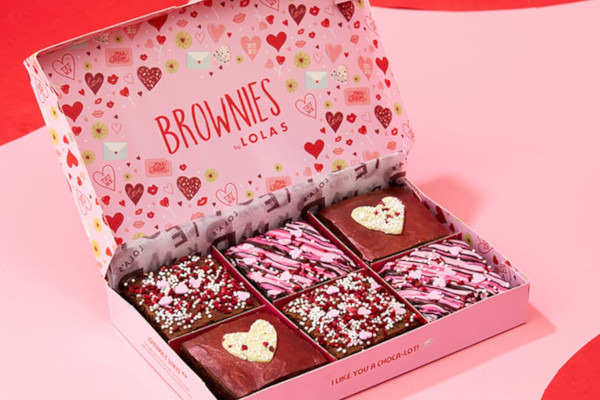 Lola's branded box with lots of hearts on filled with Valentine's themed decorated brownies