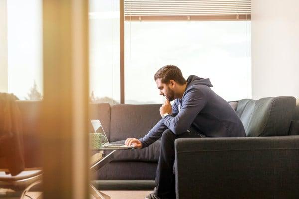 man sitting on sofa looking at laptop