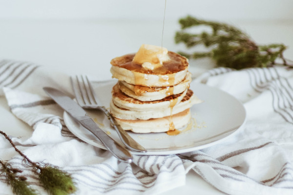 Stack of fluffy pancakes with drizzle of sauce