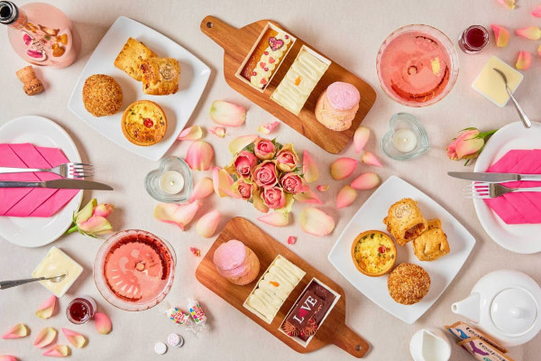 a spread of valentine's themed food items including cake and pastries