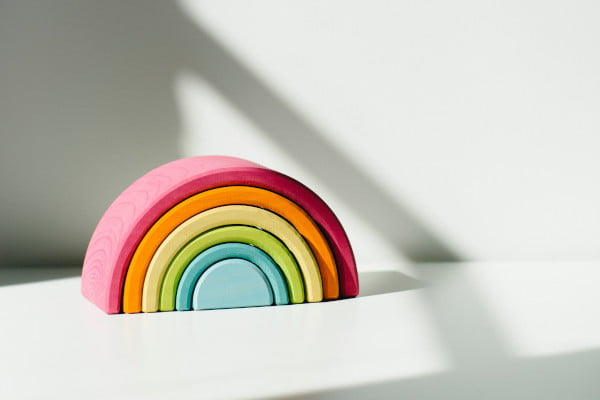 Wooden rainbow decoration on a white shelf