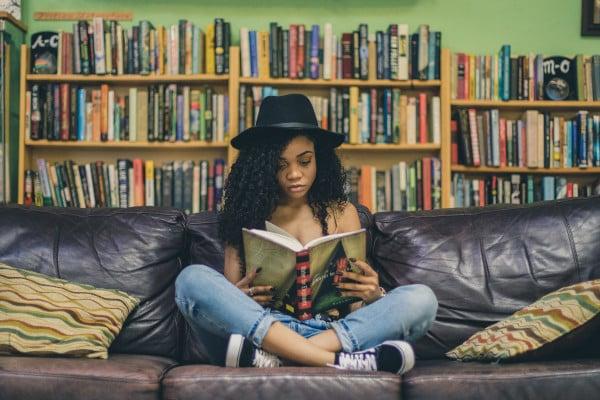 Girl reading cross-legged on the sofa, behind her are bookshelves full of books