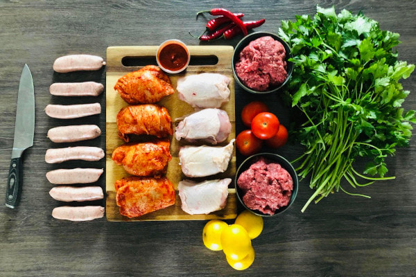 Varuious meats on a chopping board next to a knife and fresh herbs