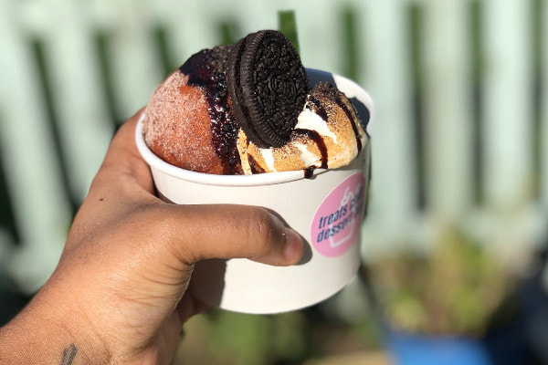 hand holding out a donut sundae in a paper tub