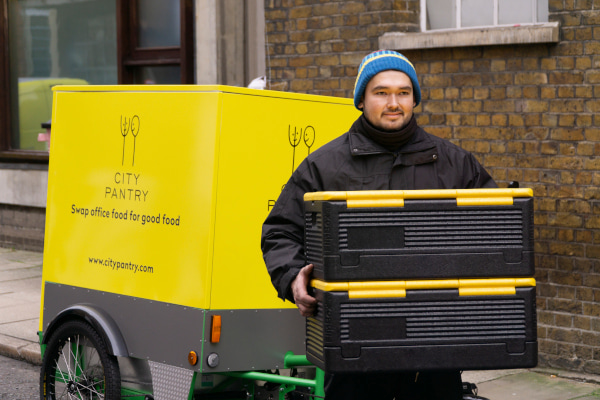 Man carrying thermal food boxes, behind him is a cargo bike